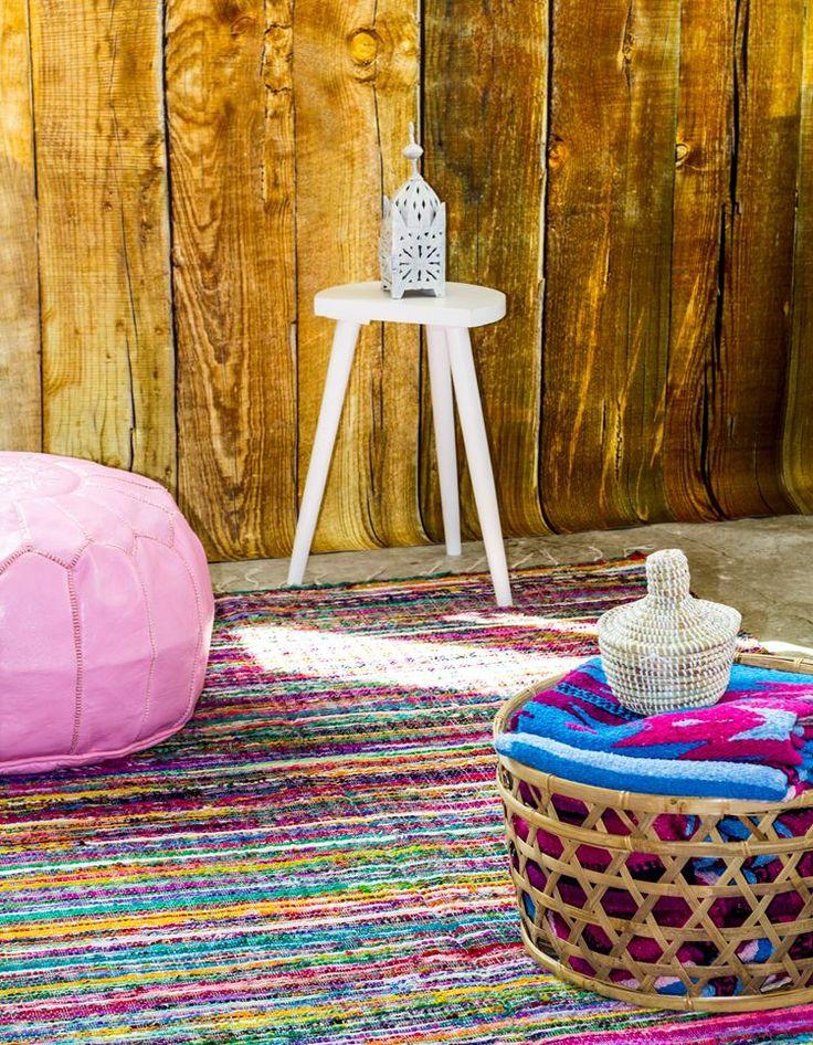 Kleurrijk vloerkleed uit India, gemaakt van gerecyclede stroken stof. Leuk met een roze Marokkaanse poef. In de mand ligt een Mexicaanse vloerkleed in mooie kleurencombinatie blauw en fuchsia. Meer op Casaquente.nl