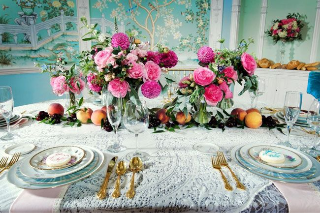 Love this table setting; gold cutlery, peaches and cherries with flowers, a lace table cloth and vintage china plates.