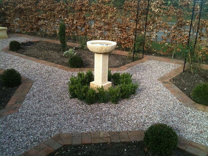 A beautifully simple hammered limestone birdbath from Foras is the central feature of the garden www.ebgardendesign.co.uk