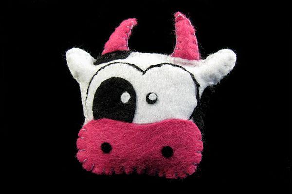 Magnes filcu krówka Mućka. Projekt własny ze szkicownika :) Rozmarzona o różowych migdałach Mućka uszyta z filcu i wypchana watoliną. Wielkość 6,5 na 7 cm z uszami i rogami.