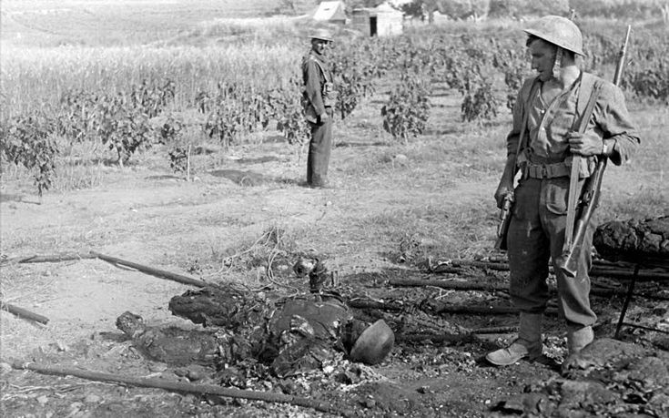 Battle of Crete, Greece May 1941: British soldiers stand by the charred remains of a German paratrooper. Such was the ferocity of resistance to the air landing German op that the paratroop division was decimated; following Crete, Hitler pulled the paras from the airborne role and send them to the Eastern Front as an infantry formation. Note the Luger held by the British soldier in the foreground.