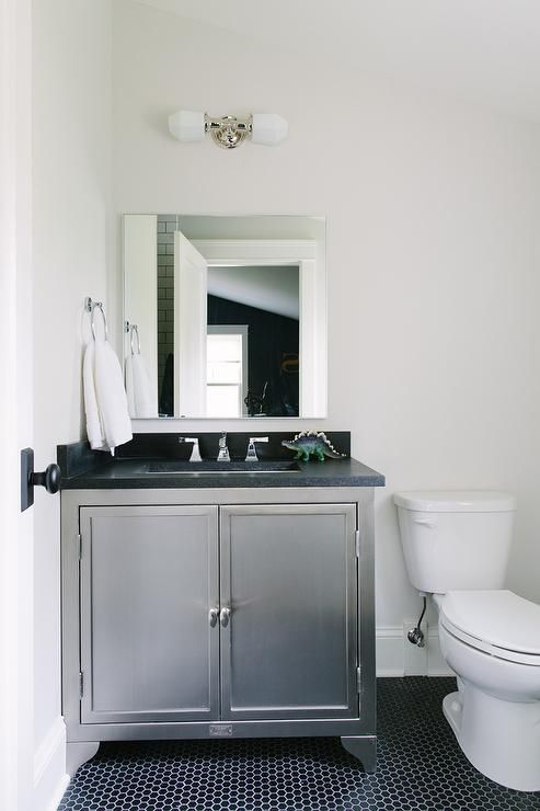 Industrial kids bathroom features floors clad in black hex tiles contrasting white walls supporting a polished nickel ring towel holder and a mounted 2 light polished nickel pendant positioned over a square vanity mirror hung above a industrial metal washstand topped with black quartz countertops holding a rectangular undermount sink and polished nickel faucet.