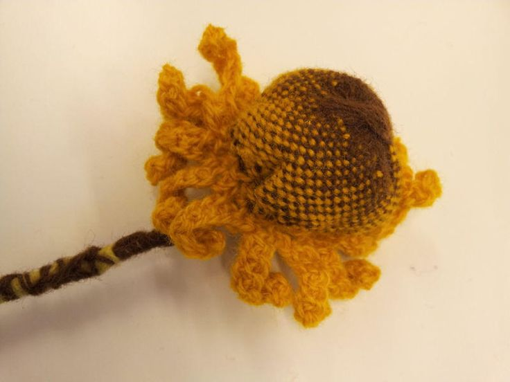Solros av enkel rundväv. Virkade kronblad. Sunflower wool circleweave and chrochet.