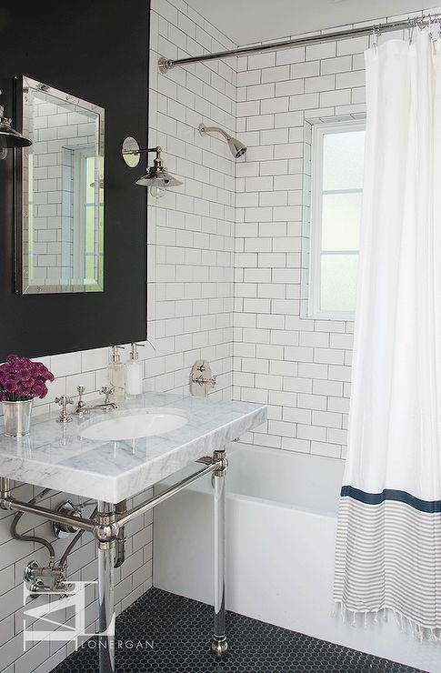 Fabulous bathroom features upper walls painted black and lower walls clad in white subway tiles with dark grout. A marble and glass washstand situated under a Restoration Hardware Rivet Medicine Cabinet illuminated by 20th C. Factory Filament Metal Sconces. A black hex tiled floor with white grout. A modern drop-in tub accented with shower tiles and finished with a striped banded shower curtains with fringe.