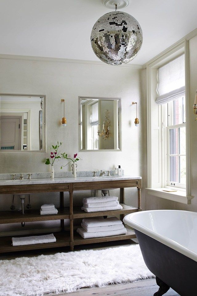 A plush alpaca rug from The Rug Company sits below a Hilary Batstone disco ball in the main bathroom.