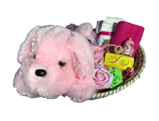 Kraammand meisjes met grote knuffelhond is een leuke kado die bestaat uit 9 kadootjes waaronder een grote ronde mand met daarin een super zachte roze hond.