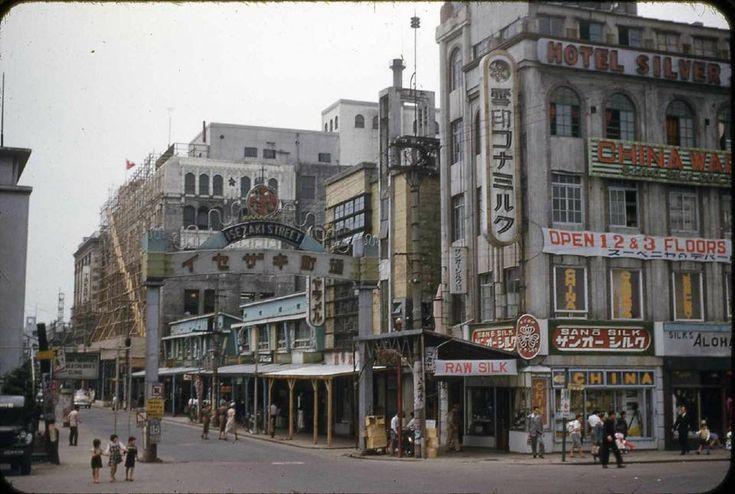 横浜・伊勢佐木町一丁目入口を吉田橋付近から撮ったものと思われます。中央やや左の女性の服装から、大正末期から昭和初期ではないかと思いますが、子供たちの服装と看板の横文字の多さから、昭和30年代以降とも思えます。左奥に見える白いビルは野澤屋(後の松坂屋)ですが、足場を組んでいるのは改修工事か。※1950年代に米軍のタイピストが撮ったものらしいということが判りました(前掲ピン参照)