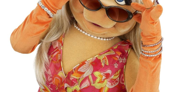 Miss Piggy brightened up her look with a paisley-printed wrap-style dress paired with orange gloves — and stacks of bling on either wrist.