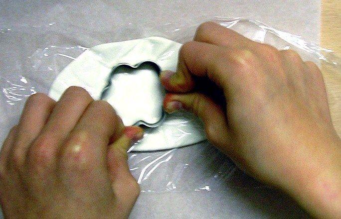 Blumen Ausstecher - Weihnachten basteln - Decken Sie die 0,5 cm dick ausgerollte weiße Modelliermasse mit Frischhaltefolie ab und stechen Sie mit einer Plätzchenform eine Blume aus. Die Frischhaltefolie dient dazu, die Ränder beim Ausstechen abzurunden...