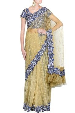 Debarun Indian Designer Lehenga Saris Online Featuring a beige net lehenga sari with gold and cobalt blue floral machine embroidered border all around. It has sequin splatter and frill hem on pallu. It comes along with a cobalt blue and gold net blouse with cutdana and thread hand embroidery. It also comes along with a blue a-line petticoat with glitter bootis all over by DEBARUN. Shop now- www.carmaonlineshop.com. #carma #carmaonline #Debarun #designer #saris #elegant #frills #beige #online