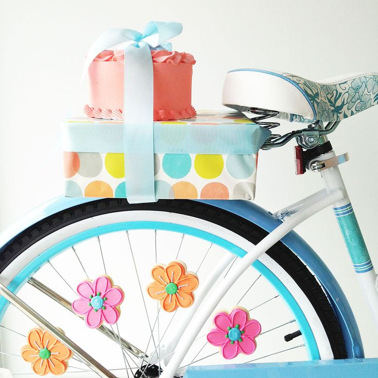 Flower sugar cookies and a coral rosette cake on a cruiser bike for Bake Sale Toronto's display windows.