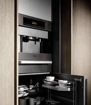appliances concealed  Limestone and graphite kitchen block island,  tall cupboards, oak veneer, sandblasted drawer doors and sliding doors from eggersmann.