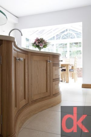 A unique oak kitchen with painted cabinetry complete with a luxury curved kitchen island and polished quartz worktops.  The curved oak kitchen island was specifically designed to enhance movement and functionality whilst enhancing the interior of this family home.  A functional boot room with storage and hanging space and wall panelling helps to complete the look.