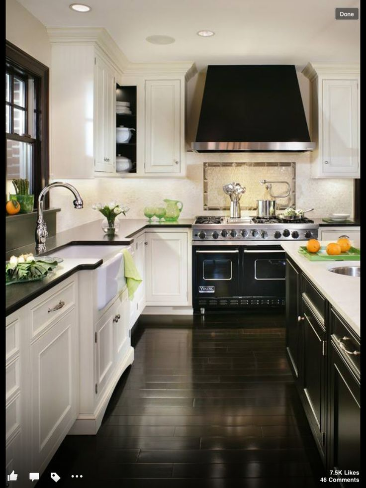 Black and white kitchen - dark floors contrasted with white cabinets. Black  counter top and black window frame.