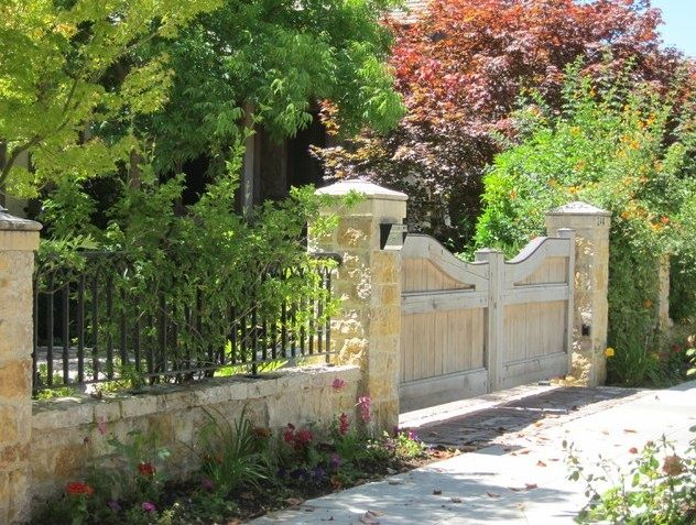 capped stone columns with raised stone wall and iron fencing. Nice heavy gate and framing on it.