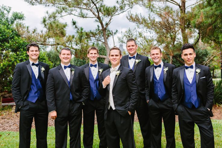 groomsmen in classic black tuxedos with navy vests and bow ties wear boutonnieres of white ranunculus.