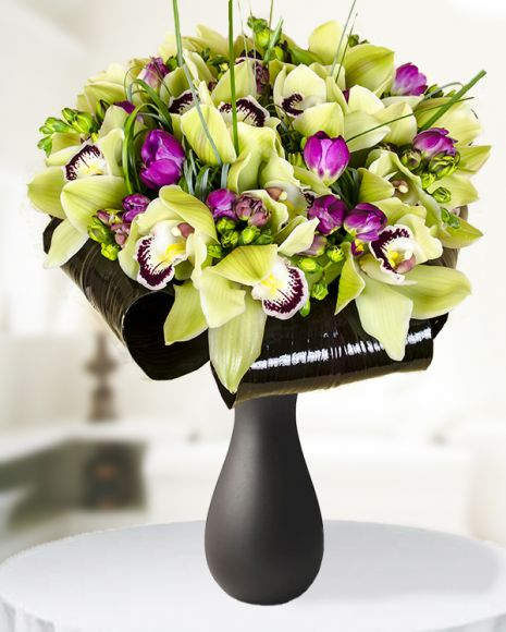 An elegant and exotic bouquet with green cymbidium orchid and cyclamen freesias, adorned with beargrass, cordyline leaves and tied with a satin ribbon.