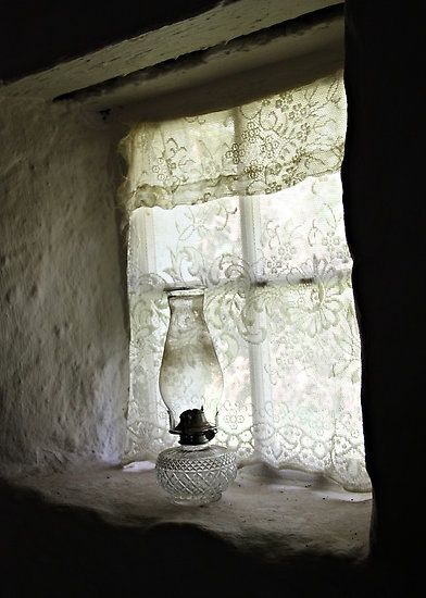 Love the Oil Lamp, recessed stone window sill, old fashioned lace curtains