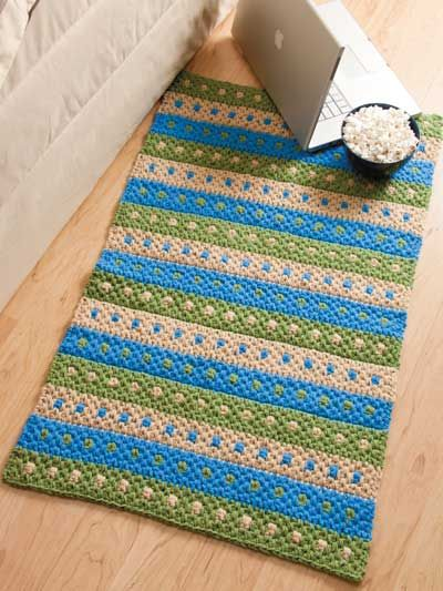 """Brighten your decor with this cheery throw rug design that uses simple color changes to create a pretty striped pattern. This e-pattern was originally published in the August 2011 issue of Crochet World magazine. Size: 24"""" x 40"""". Made with medium (worsted) weight yarn and size N (10mm) hook.Skill Level: Easy"""
