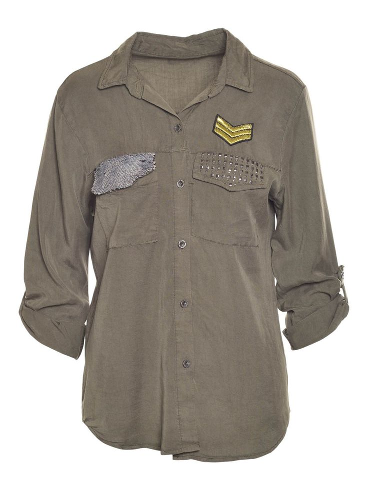 Hemd met knopen en lange mouw. De mouw kan je omplooien door middel van een lintje. De pijpzakjes zijn versierd met zilveren glitter pailletten en grijze studs. De pop draagt een TU.