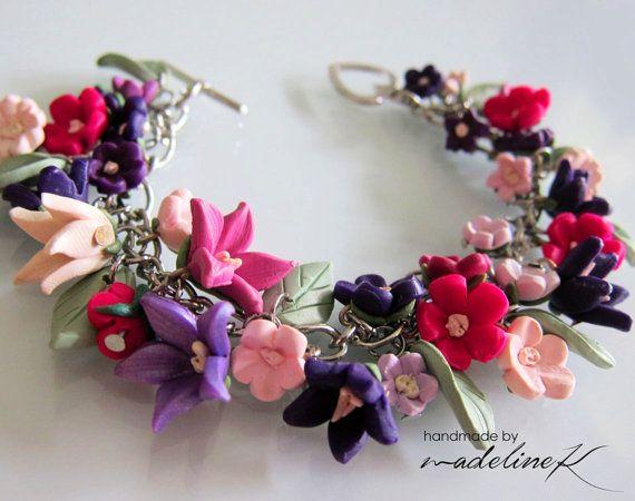 Questo favoloso braccialetto floreale è riccamente dettagliato, con una varietà di fiori argilla polimerica a mano libera. I fiori, di varie dimensioni, sono apposto su una catena portacavi. Foglie verde pallido striate, fatta anche di argilla polimerica, sono armonicamente tra i fiori.  I fiori su questo braccialetto sono incantevoli sfumature di rosa pallido, lavanda, crema, viola e fucsia. I fiori più piccoli misurano circa 0,25 pollici di larghezza, mentre i fiori più grandi misurano…