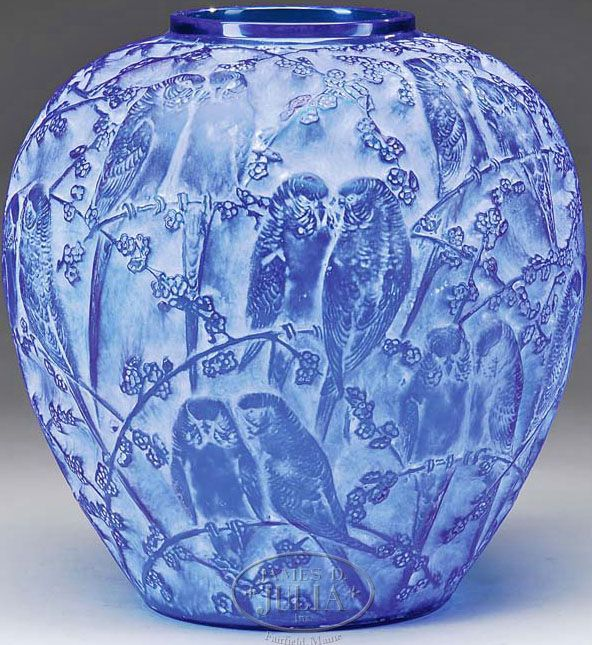 """Blue Lalique Glass Vase. An R. Lalique vase in the Perruches pattern has deeply impressed parakeets side by side on flowering branches surrounding the entire vase. Vase is done in a beautiful rich blue glass and finished with a white patination. Signed on underside with impressed block letters """"R. Lalique"""" 1914 - 1924"""