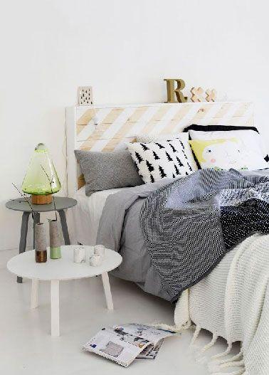 Plus sophistiquée, une tête de lit dont l'épaisseur de la palette est cachée par une baguette bois avant de recouvrir plateau et bords d'une peinture blanche appliquée en bandes sur la diagonale de la palette de manière à conserver une partie du bois clair apparent.