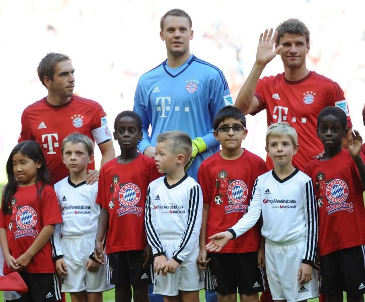 Back row from left: Munich players Philipp Lahm, goal keeper Manuel Neuer and Thomas Mueller pose with migrant and refugee children before the German Bundesliga soccer match between FC Bayern Munich and FC Augsburg at the Allianz Arena in Munich, Germany, Saturday Sept. 12, 2015. (Andreas Gebert/dpa via AP)