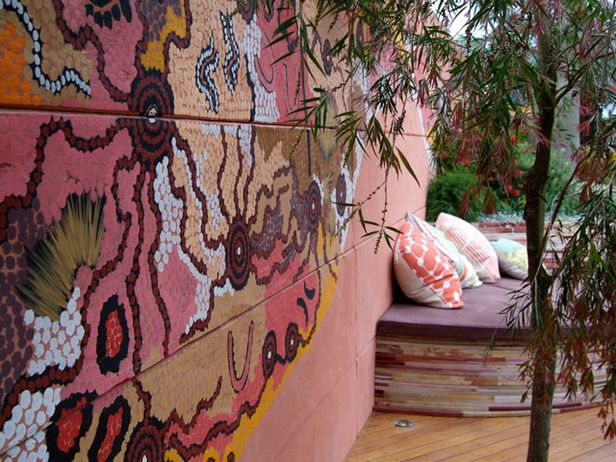 Turn an outdoor wall into a canvas. This mural, by renowned aboriginal artist Gabriella Possum, adorns the wall surrounding a large outdoor room, bringing color and organic curves to the space. Design by Jamie Durie.