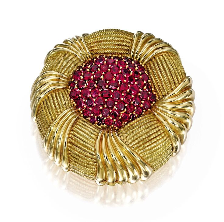Bunny Mellon  Schlumberger Gold and Ruby Compact AN 18 KARAT GOLD AND RUBY COMPACT, SCHLUMBERGER FOR TIFFANY & CO. – Designed as a flowerhead centering a cluster of round and cushion-cut rubies, gross weight approximately 110 dwts, the interior 8 tted with a mirror and compartment, signed Tiffany – Schlumberger.