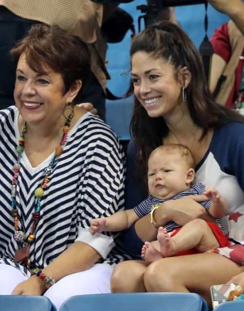 The family of the United States' Michael Phelps, mother Debbie, left, and his fiance Nicole Johnson holding their baby Boomer watch the swimming competitions at the 2016 Summer Olympics, Monday, Aug. 8, 2016, in Rio de Janeiro, Brazil.