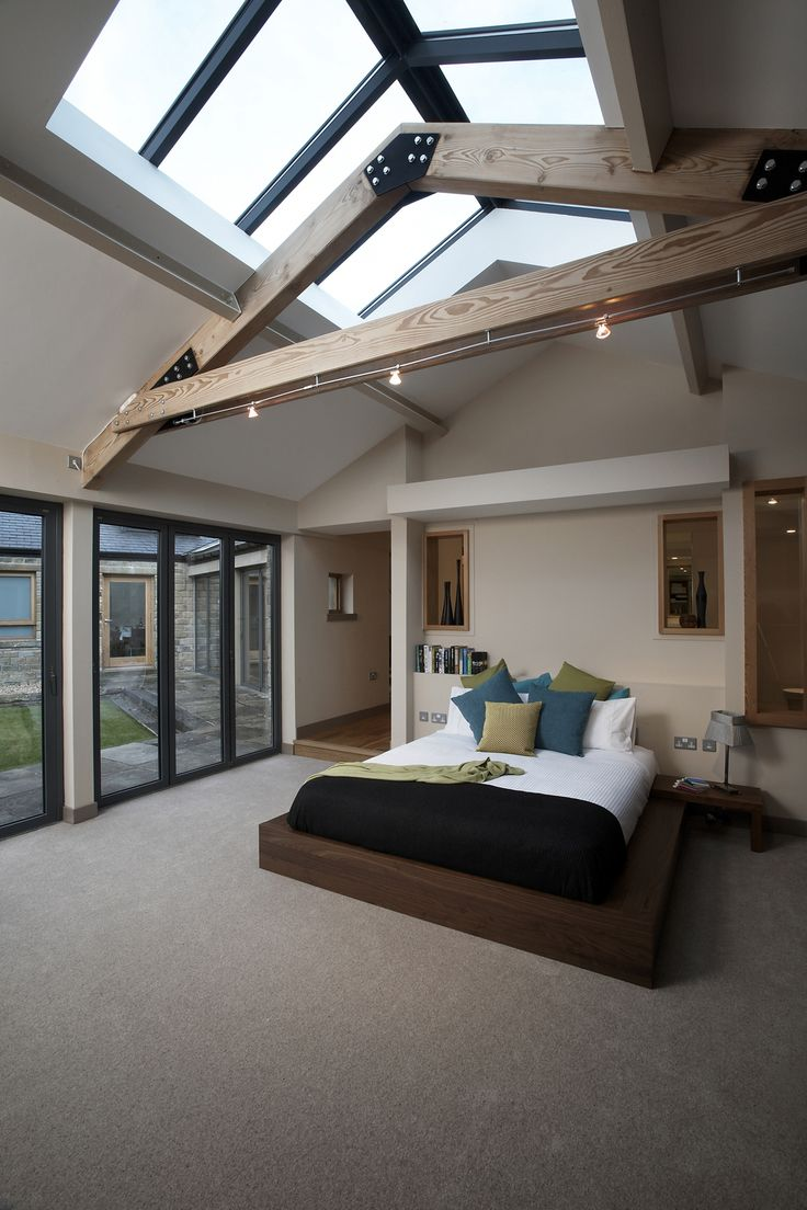 Contemporary master bedroom by One 17. Timber trusses. Rooflights. Solarlux bi-folding screens. BoConcept bed. Openings into ensuite.