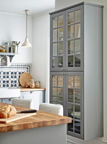 Vitrine aus Küchenschränken; FAKTUM Wandschrank mit Lidingö Vitrinentüren in Grau in einer Küche mit Kücheninsel
