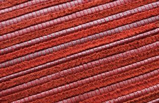 A close-up of 'Zebrano - Lollipop' by Limited Edition. Zebrano is made out of traditionally woven leather. | www.le.be | Collection 2015 #bespoke #rugs #carpets #madeinbelgium #rawmaterials #red