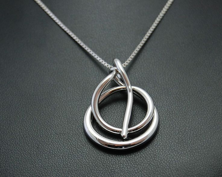 Necklace with pendant that draws a sine. Electroformed copper, silver plating and rhodium.
