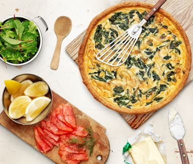 En krämig paj med spenat och lagrad smakrik ost är ett utmärkt sällskap till kallrökt lax. Spenat- och ostpajen är snabbt tillagad med hjälp av färdig pajdeg. Servera den vackra pajen ljummen till den rökta laxen och en sallad.