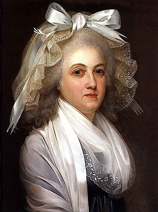 Marie Antoinette wears a high waisted dress with a scoop neckline under her fichu. She wears a lace cap adorned with a ribbon and bow. 1792 a year before her death