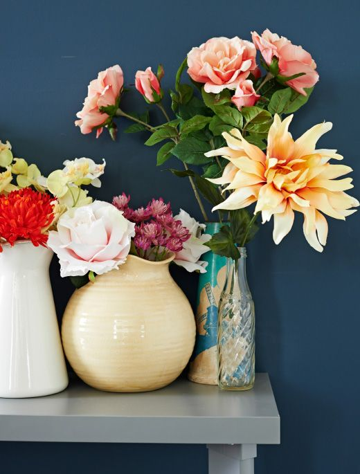 Collection of colorful artificial flowers in a group of vases on hall table. Blue wall in background.