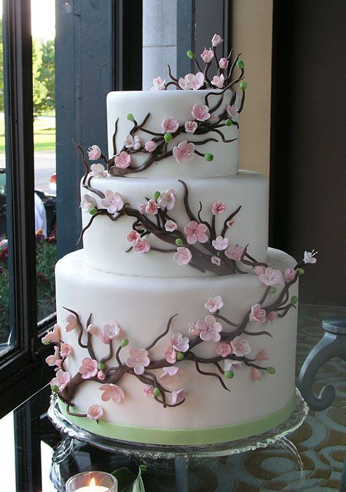 Cherry Blossoms - This cake dressed in frosting cherry blossoms is the perfect fit. The botom tier consists of four full cake layers and three layers of filling, making it twice the height of either of the other two tiers.