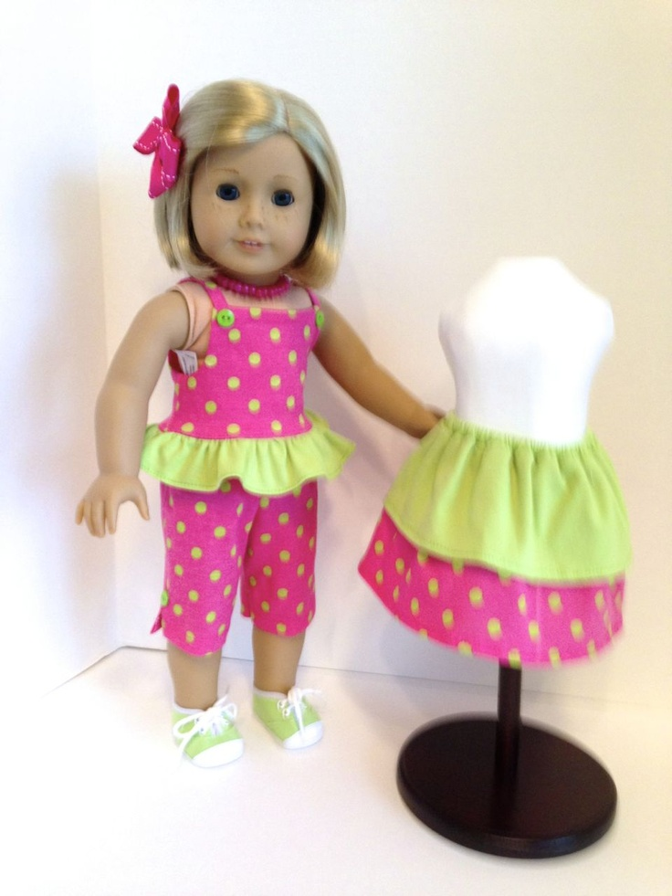 This three piece summer outfit is made of knit with a ruffle surrounding the strap top which has green button accents. The skirt has two tiers of solid green and pink dots. The crop pants have slits at the hem and both the top and pants have green button  accents. The hot pink beaded necklace, hair bow and green tennis shoes complete the outfit.