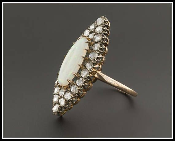 Sorry been tied up all day .. I will be back in town in an hour and will come by a then😛I was actually up sthere going to text you lady its rainbow flashes of color. This ring (circa 1890-1910) features a white oval opal cabochon with flashes of orangey peach and green