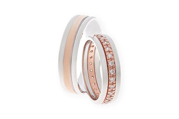 Tyto luxusní snubní prsteny jsou v kombinaci červeného a bílého zlata ve vysokém lesku. Tvoří je tři spojené obroučky, kdy prostřední část je z červeného zlata. Dámská varianta má po celém obvodu vsazeny velké kameny.