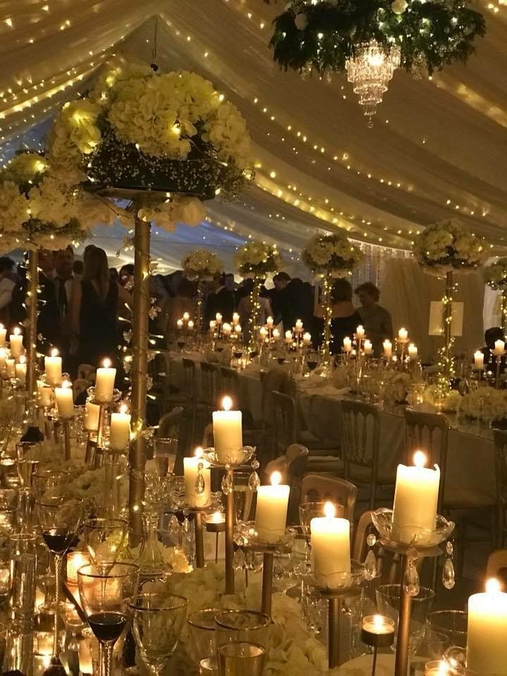 winter wedding marquee. candles and white flowers with ...