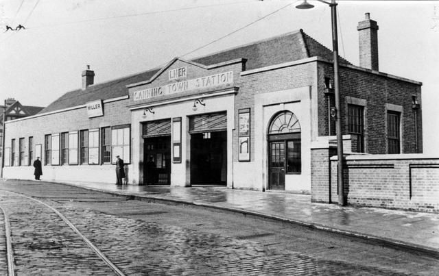 """Canning Town Station, 1933. The station was opened by the Eastern Counties and Thames Junction Railway as """"Barking Road"""" in 1847, and was situated to the south of the road. It was rebuilt on the same site in 1873 and renamed Canning Town. The station was again re-built north of the Barking Road in 1888, being further rebuilt in 1932 and 1979. A replacement booking hall was constructed in the 1960s and was demolished in 1994."""