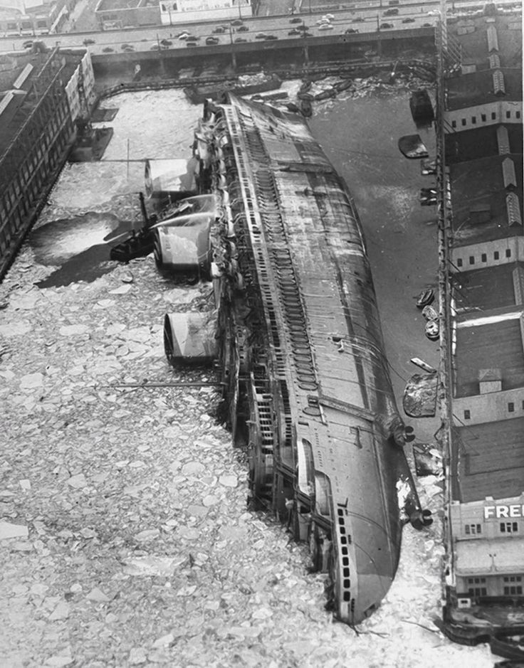 The luxury ocean liner SS Normandie lies capsized in the icy Hudson River after catching fire. c.1942