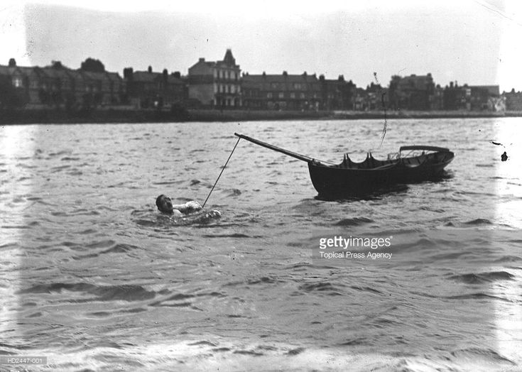 """Jules Gautier, is a prime example of the Victorian exhibitionist swimmer. Born in 1856 and a pianoforte maker by trade, he was known as """"the champion of France"""", although in fact he hailed from Islington. In 1909 he was still swimming the Thames manacled, only this time he swam the university boat race course from Putney to Mortlake, """"towing a boat [pictured here] licensed to carry eight persons""""."""