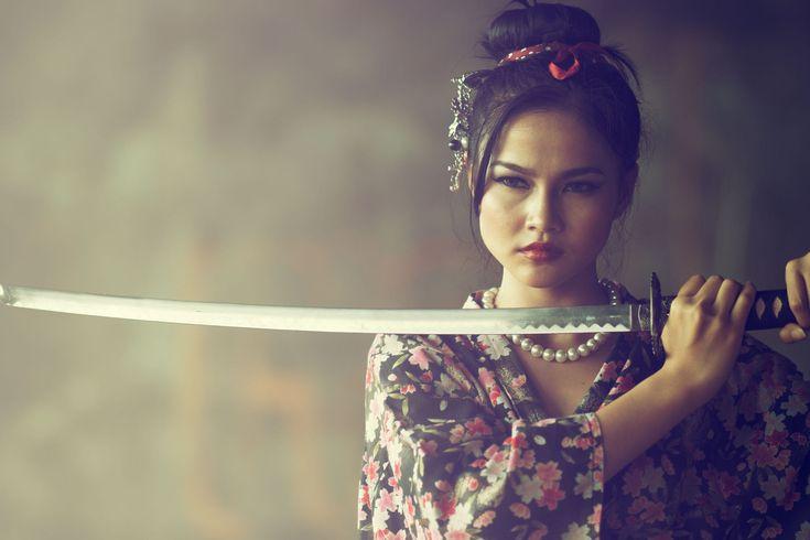 An Asian girl is holding a katana sword