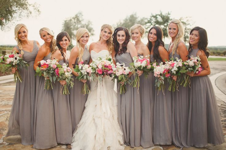 bridesmaids in floor length grey gowns carry loosely tied and wild bouquets of chocolate cosmos, pink dahlias, pink roses, pink lisianthus, pink ranunculus, cream roses, white stock, white ranunculus, seeded eucalyptus and lemon leaf.