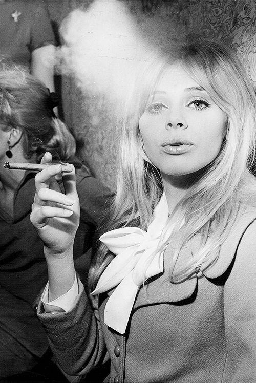 Britt Ekland smoking a cigar at a London Exhibition, 1966