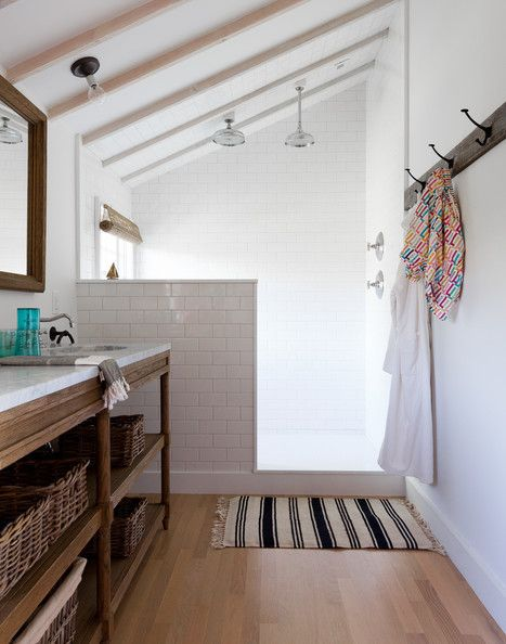 Beautiful bathroom that might be in an attic, based on the slanted ceiling. White subway tile, weathered oak vanity.